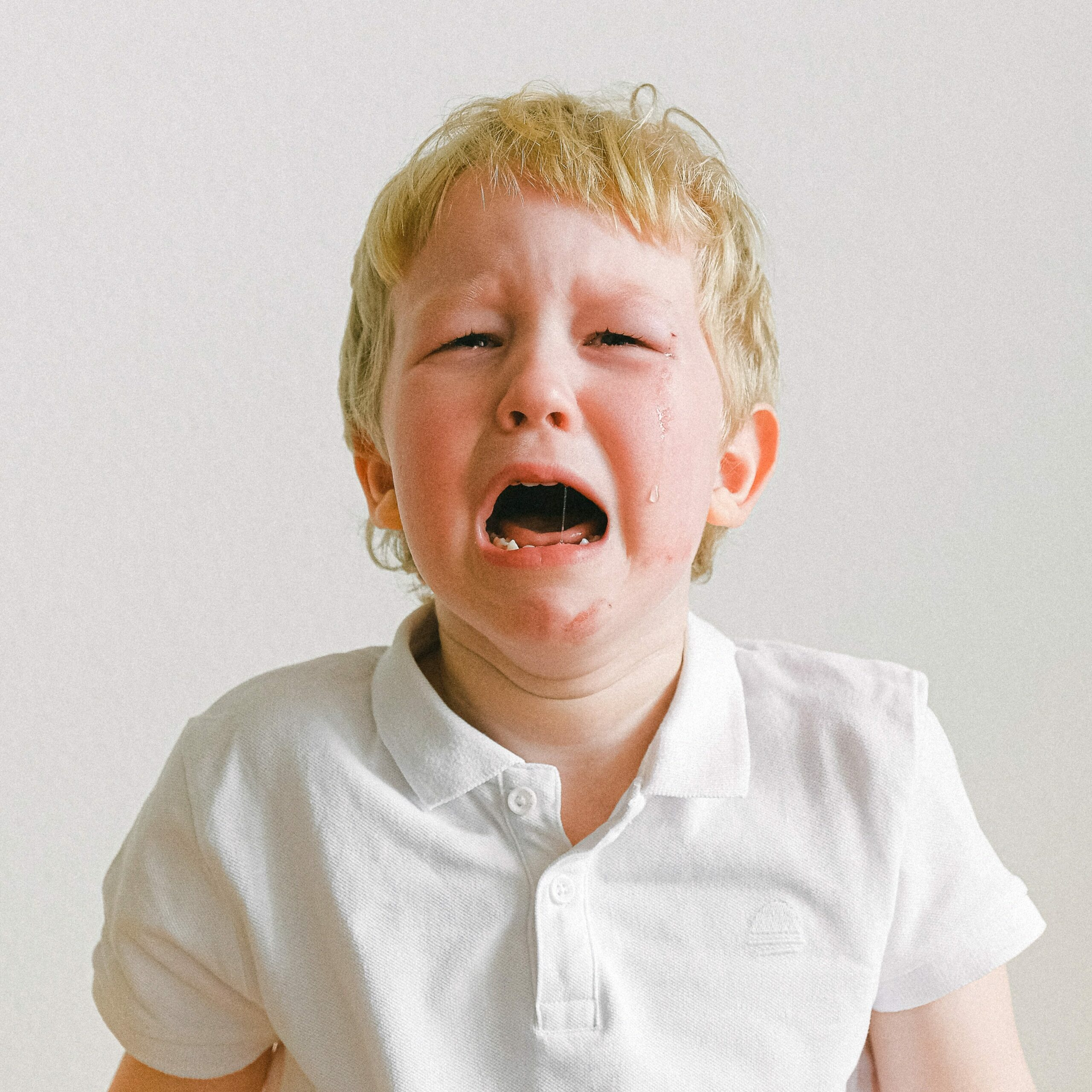 Picture of a crying boy with a white shirt in front of a white wall