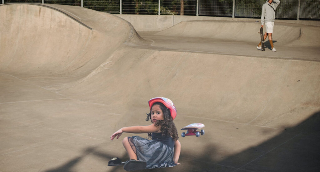 A young girl with a pained expression is on the ground with a skateboard nearby as an older skateboarder is in the distance with a hand on his head